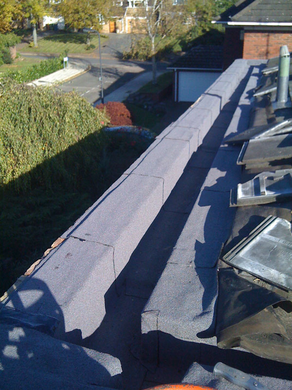 The capsheet extends under the pitched roof tiles and the top of the parapet wall.